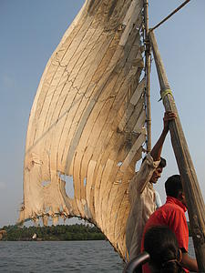 On board a sailing boat with a worn out sail in Jaitapur, Maharastra, India.