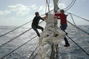 Furling a sail in the front of the ship.