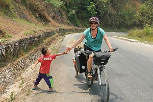 Sandra greeting a kid by the roadside in Laos.