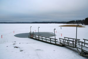Ice swimming place and a lonely skier on the Laajalahti bay, Helsinki, Finland.
