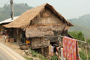 A typical bamboo hut in a Lao village, modernized with a satellite TV receiver.
