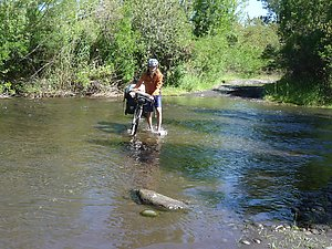 Arto crossing a river on a small gravel road.